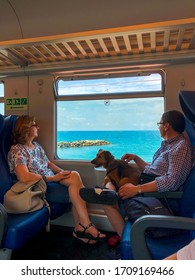 Couple of italians riding on a train with their dog and looking at a seaside view through the window. Liguria, Genoa, Italy. June, 2018.