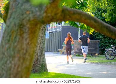 Couple jogging in the leafy avenues of Vondelpark