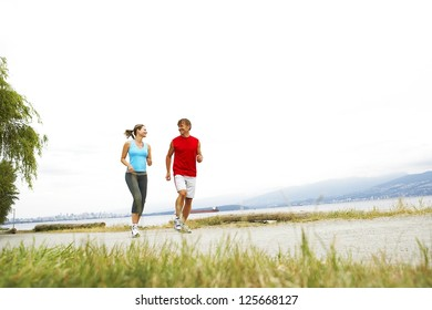 couple jogging outside, grass visible on the foreground, mountains and bright sky visible in the background