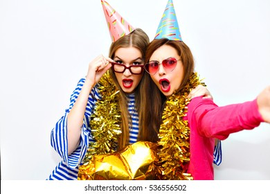 Couple of joyful cute girls in colorful clothes, funny birthday hats and stylish glasses, taking selfie on smartphone while celebrating birtday. Amazing party. Isolated background.