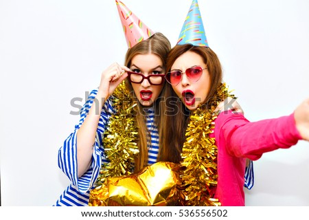 Couple Of Joyful Cute Girls In Colorful Clothes Funny Birthday Hats And Stylish Glasses