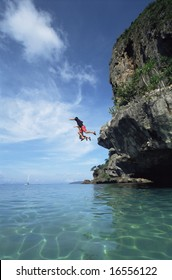 Couple jumping from cliffs into the sea