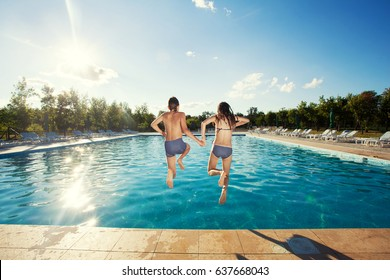 Couple jumping into pool. Summer vacations
