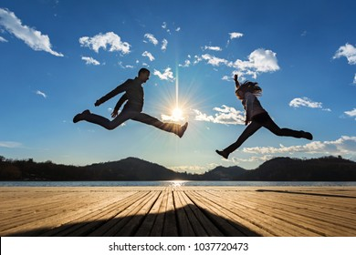 couple jumping in the sun on the dock of a lake