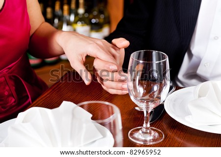 Couple, just hands to be seen, is holding hand while waiting for their food and drinks in a restaurant.