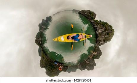 Couple in kayak on Ha Long Bay in Vietnam among rock karst formations in 360 little planet.