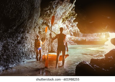 Couple of kayakers stands with kayak and paddles at entrance to sea cave
