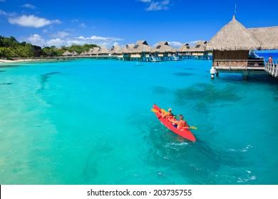 Couple kayaking in the blue lagoon, Bora Bora, French Polynesia, South Pacific