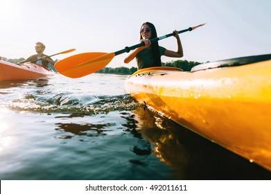 Couple kayaking. Low angle view of beautiful young couple kayaking on lake together and smiling