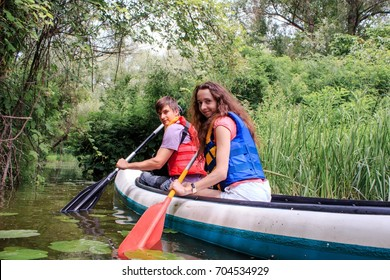 A couple kayaking on a stream in a forest spending their leisure time with fun
