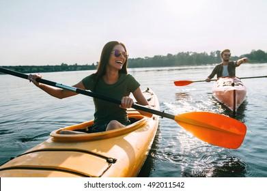 Couple kayaking together. Beautiful young couple kayaking on lake together and smiling
