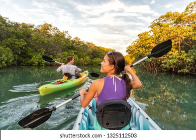 Couple kayaking together in mangrove river of the Keys, Florida, USA. Tourists kayakers touring the river of Islamorada.
