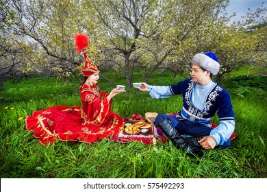 Couple in Kazakh costume sitting in Spring Blooming apple garden at picnic and drinking tea in Almaty, Kazakhstan, Central Asia