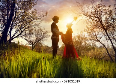 Couple in Kazakh ethnic costume in silhouette in Spring Blooming apple garden at beautiful sunset