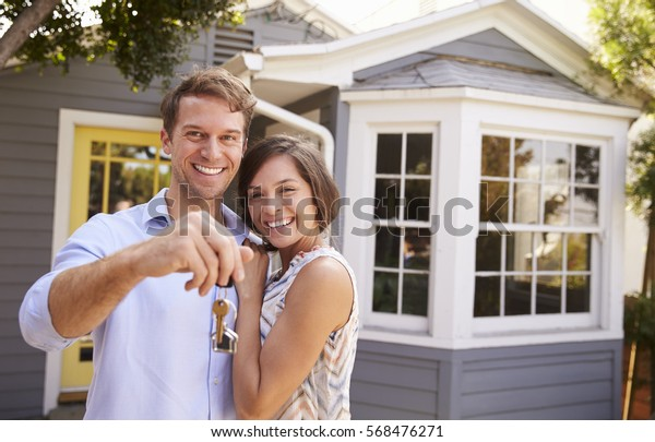 Paar mit Keys, die außerhalb des neuen Zuhause stehen