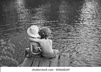 couple of kids seating on the beach, child whispering on wooden platform, summer spring sunny morning, jetty on the water lake background, vintage black and white, The boy hugs the girl from the back