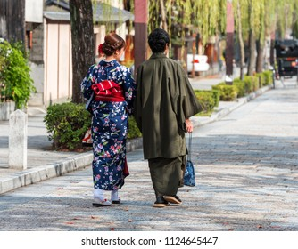 Couple in a kimono on a city street, Kyoto, Japan. Back view