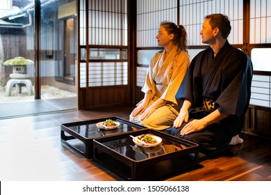 Couple in kimono seiza sitting at traditional Japanese home ryokan room by table plates by shoji sliding paper doors, looking at peaceful garden with stone lantern
