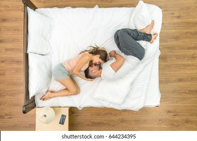 The couple kiss in the bed. View from above
