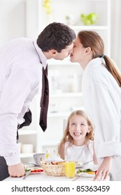 A couple kisses in front of the child