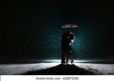 Couple Kisses Under Umbrella While it is Snowing Outside