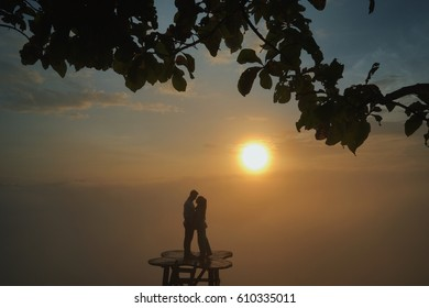 a couple kissing captured during sunrise at bukit panguk,jogjakarta