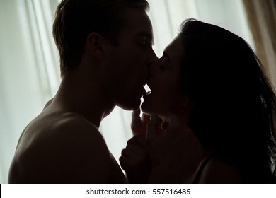 Couple kissing in the dark. Man and woman indoor. The passion between us.