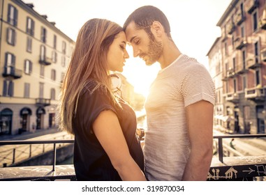 couple kissing each other on a bridge over the river. concept about passion and love