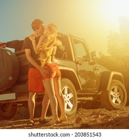 A couple kissing next to a 4x4 car on sunset