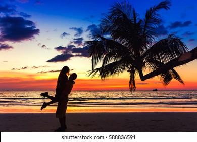 Couple kissing on the beach with a beautiful sunset in background, man lifting the woman on background sea ocean water and colorful sunset sky / Vacation couples in tropical paradise / Bali, Indonesia
