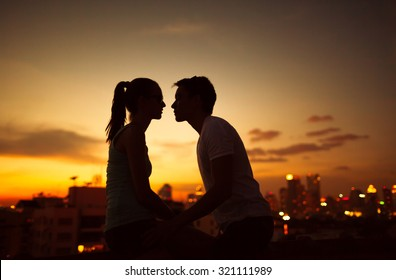 Couple kissing on a city roof top.