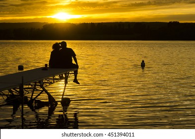 A couple kissing on the pier at sunset on Struthers Lake, Saskatchewan