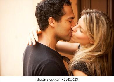 A couple kissing outdoors in an European urban setting