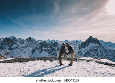 Couple kissing in the snow. Young couple in love kissing on top of a mountain. Les 2 Alpes, French Alps