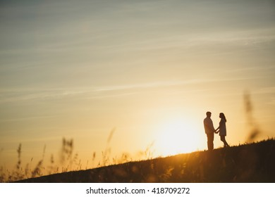 Couple kissing at sunset. silhouette of a loving couple at sunset in a wheat field.