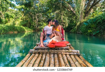 Couple kissing and taking a romantic ride down Martha Brae river, on bamboo raft. Sweet honeymoon vacation in Montego Bay, Jamaica, Caribbean.