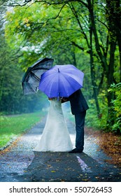 couple kissing under umbrellas