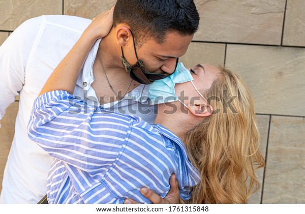 a couple kissing wearing masks, a conceptual and provocative image of the new normality after the covid19 epidemic period, love at the time of the pandemic