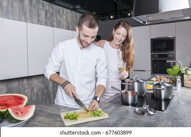 couple in the kitchen cooking vegetable soup he prepares some chili and she is drinking wine. they have a modern kitchen with grey concrete desk and glossy finish white cabinets. they wear white tops.