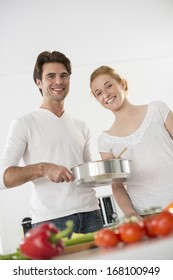 couple in the kitchen cooking vegetables