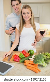 Couple in the kitchen drinking wine with vegetables on chopping board