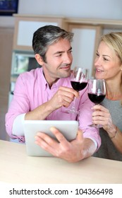 Couple in kitchen with glass of wine websurfing on tablet