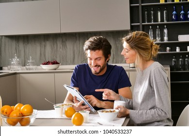 A couple in the kitchen looks at the tablet with the souvenir photos of their holidays or of the past times while having breakfast and smiling happily. Concept of: family, technology, memories.