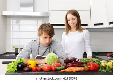 Couple in kitchen - Man unhappy with cooking sitting and woman