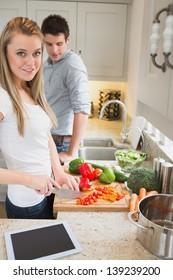 Couple in the kitchen with tablet computer preparing vegetables