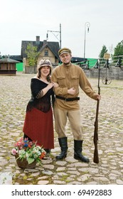 Couple of lady and soldier shown on retro-style picture. Costumes accord the times of World War I. Photo made at cinema city Cinevilla in Latvia.