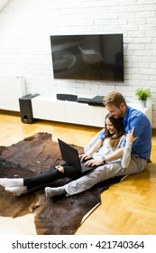 Couple with a laptop sitting on the floor