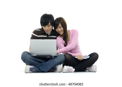 Couple with laptop, sitting on floor