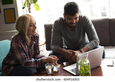 Couple with laptop spending time at coffee shop