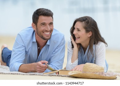 couple laughing about the story on the book